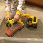 Indoor Sandbox - child playing with trucks in sandbox