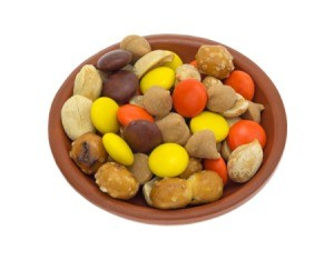 Snack mix of orange, brown, and yellow candies, butterscotch chips, pretzel nuggets, and nuts