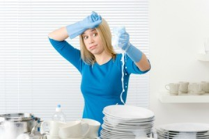 Woman with stacks of clean dishes squeezing soapy water from sponge with an overwhelmed expression