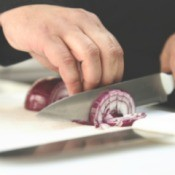 Chef chopping red onion
