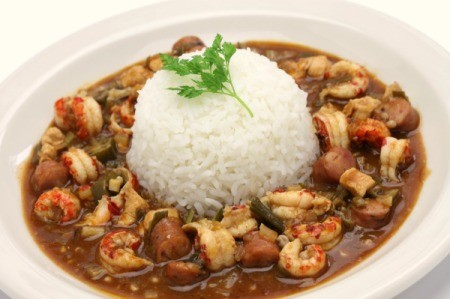 Mound of rice surrounded by shrimp gumbo.