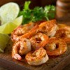 Canjun grilled shrimp with lime on a wood board.