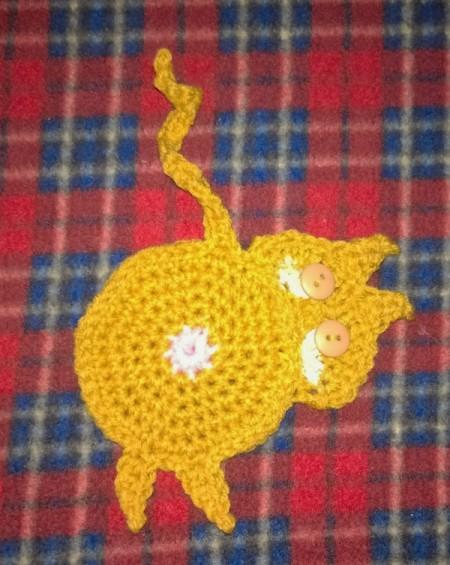 Crochet coaster of a cat looking back over its shoulder.