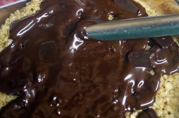 Chocolate being spread on top of a dessert.