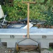 Reel mower leaning on tool box.