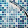 Shower head in blue tiled shower enclosure.