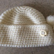 white knit hat with circle pin on folded up bottom