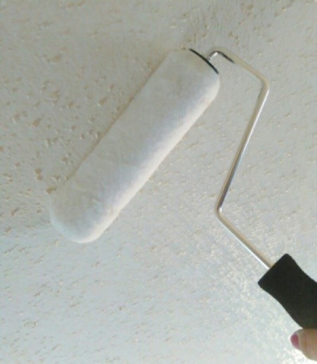 Using a paint roller to clean ceiling.