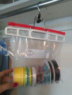 Ziploc bag of ribbon spools handing on a closet rod.