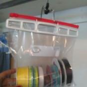 Ziploc bag of ribbon spools handing on a closet rod.