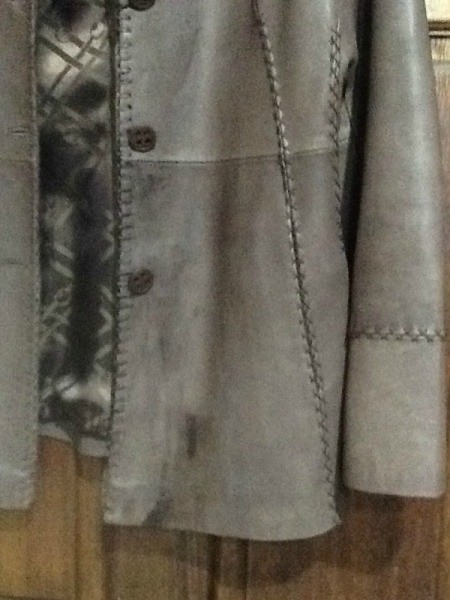 Several dark stains on gray leather jacket.