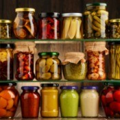 A shelf full of jars of preserved fruits and vegetables.