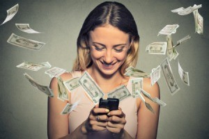 A woman with money flying out of her smartphone.