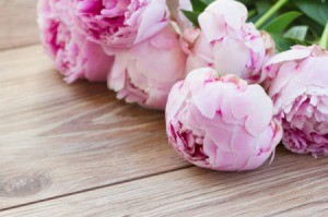 A bunch of fresh peonies on a wood floor.