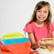 A girl eating lunch out of her lunch box.