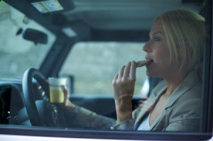 A woman eating breakfast in her car.