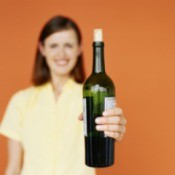Woman holding out a partially empty bottle of wine with a cork partially reinserted