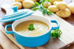 Bowl of potato soups surrounded by potatoes