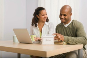 Couple looking at recipes both online and using recipe box