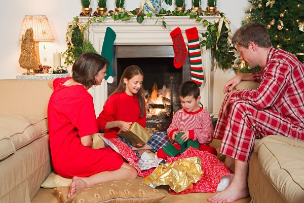 a young boy opening presents with his family on christmas morning