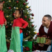 A family opening present on Christmas morning around the tree.