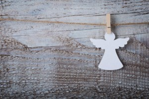 A paper angel cutout hanging from a clothespin.