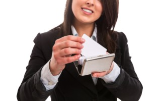 A woman placing a business card in a holder.