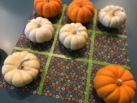 Tic Tac Toe game board and mini pumpkins for the Xs and Os