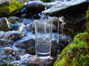 A glass catching clear spring water.
