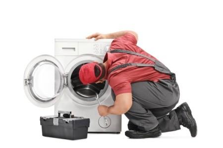 A repairman looking at a washing machine.