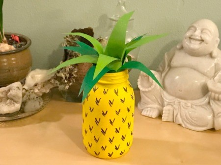 glass jar painted like a pineapple with paper leaves