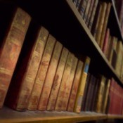 Old books lined up on a bookshelf.