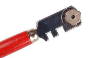 A photo of a glass cutter with a red handle.