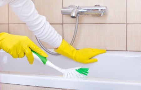 Someone cleaning a tub with rubber gloves on.