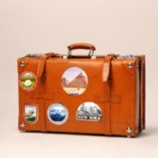 A leather suitcase with travel stickers.