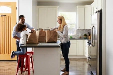 A family unpacking groceries in the kitchen.