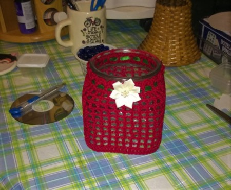 A crocheted covered candy jar.