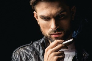 A man smoking a cigarette and wearing a black leather jacket.