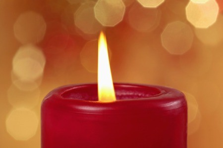 A burning red pillar candle.