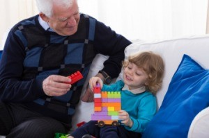 A grandfather playing blocks with his granddaughter.