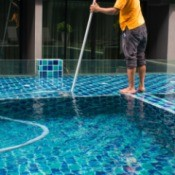 A man cleaning a swimming pool.