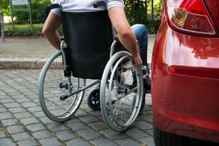 A man in a wheelchair getting into a car.