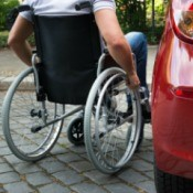 A man in a wheelchair getting into a car.