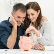 A couple putting money into a piggy bank.