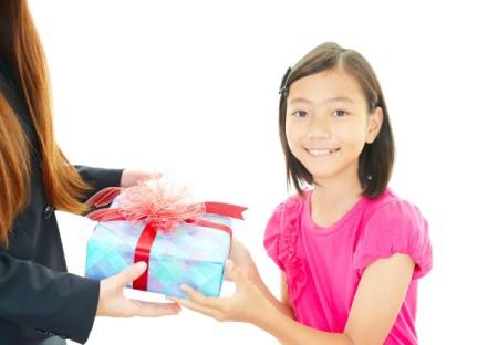 A girl giving her teacher a gift.