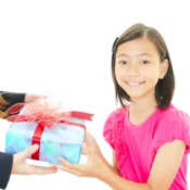 A girl giving her teacher a gift.