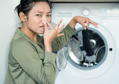 A woman washing stinky clothing.