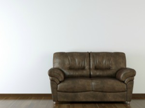 A brown leather sofa on a wood floor in front of a white wall.