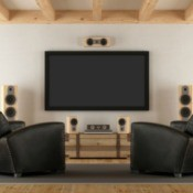 Two black armchairs facing a screen and speakers.