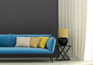 A blue couch on a dark gray wall.
